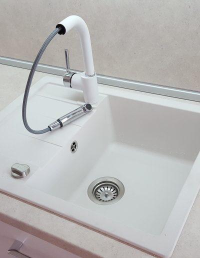 Смесителят е в цвят бяло и хром и е с изтеглящ се душ.