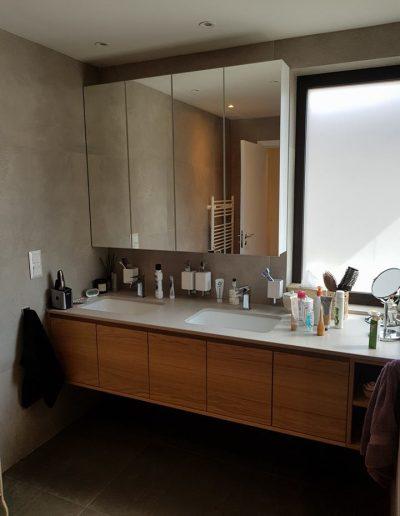 Долният шкаф за баня е с корпус от ПВЦ и вратички от МДФ фурнир. Плотът е от технически камък с две вградени мивки. Горният шкаф е изцяло от ПВЦ, вратите са му с огледала.