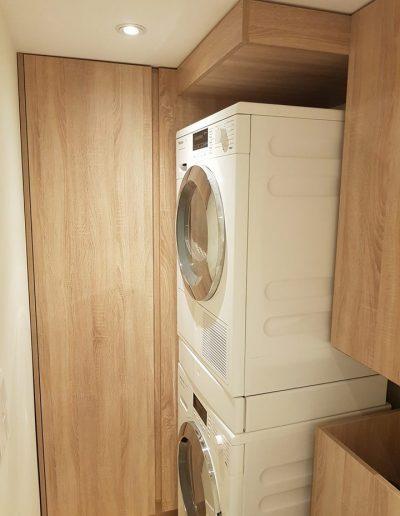 В пералното помещение в сутерена е монтиран висок шкаф за съхранение, а тръбата за мръсни дрехи, която се спуска от най-горния етаж е облечена с плоскости. Под нея е поставен и кош за пране на колелца.