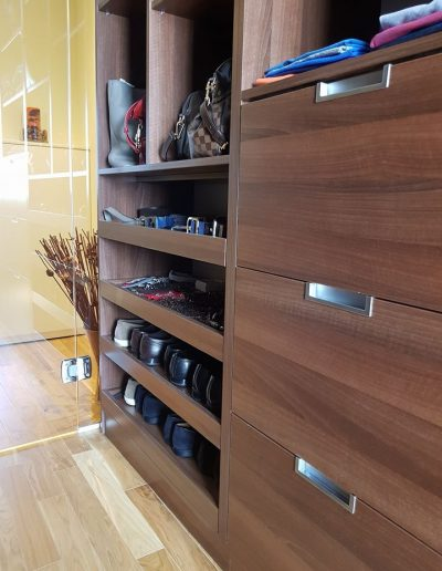 Гардеробното помещение към основната спалня е изработено от ПДЧ орех Аида Табак. За чекмеджетата, както и за изтеглящите рафтове за обувки са използвани механизми с пълно изтегляне и плавно прибиране на фирма Hettich.