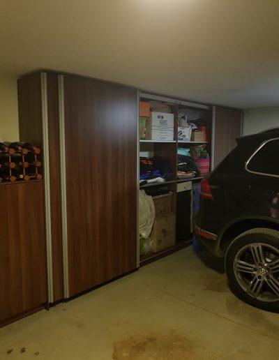 Гардеробът в гаража е направен от ПДЧ орех Аида табак на фирма EGGER. Използваната плъзгаща система Top Line L Syncro на Hettich, позволява двете предни врати да се отворят едновременно в противоположни посоки, което на практика позволява достъп до половината гардероб само с едно движение.